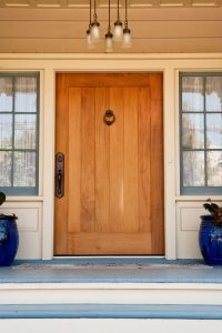 A wide, wooden front door on an upscale home with view of side panel windows. Vertical Shot.